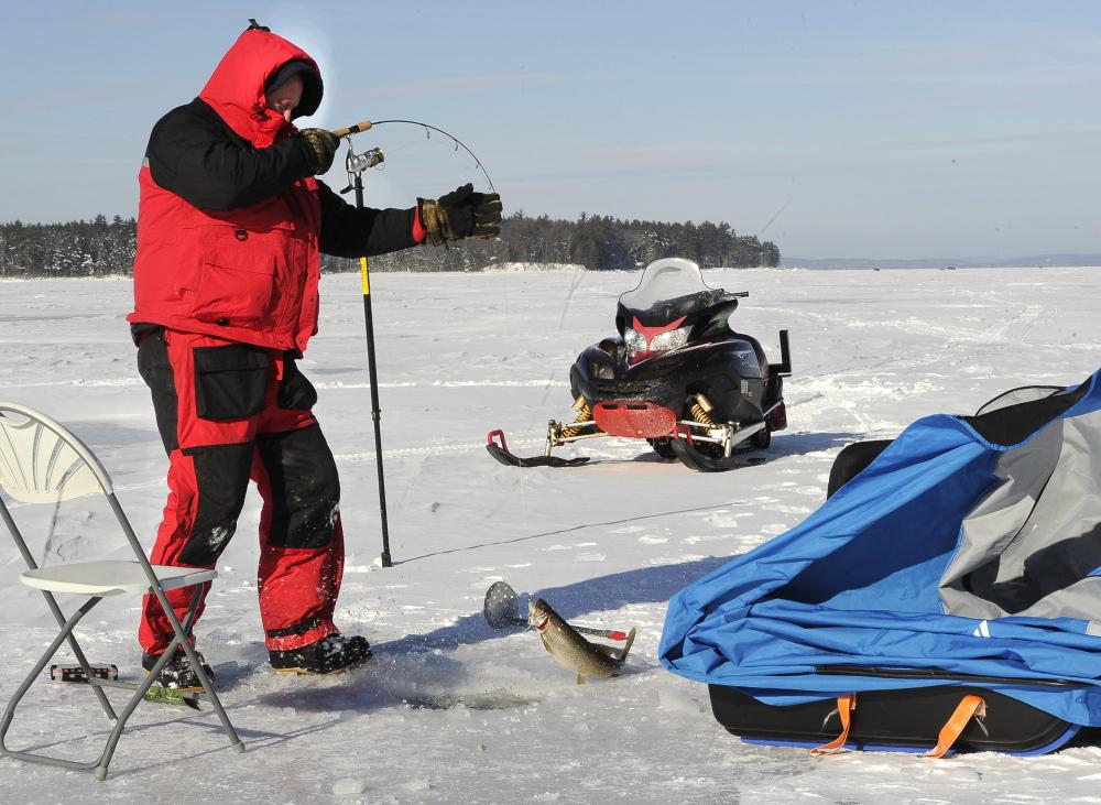 Steve Howland of South Portland hauls in a togue on Sebago Lake.