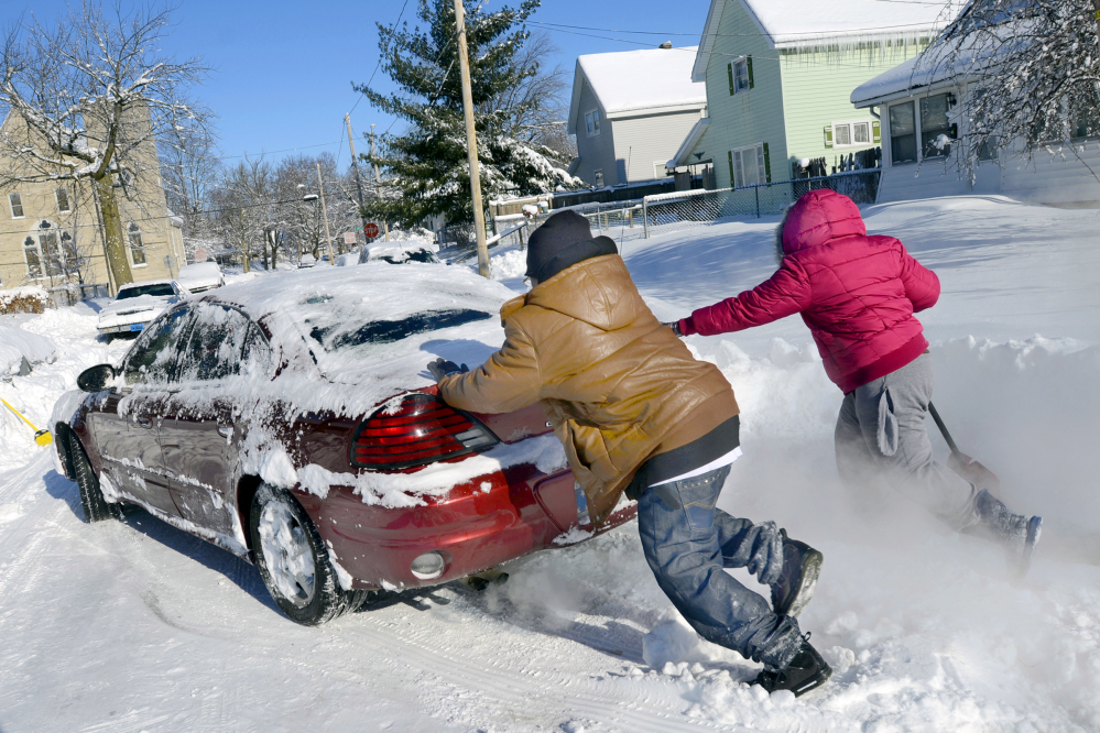 Anton Marble and his sister, Tamika, help their mother, Jaina McGee, free her car from the snow in Marion, Ind., on Tuesday, Jan. 7, 2014. More than 13 inches of snow fell on the area as temperatures plunged to a record 14 below zero Monday night.