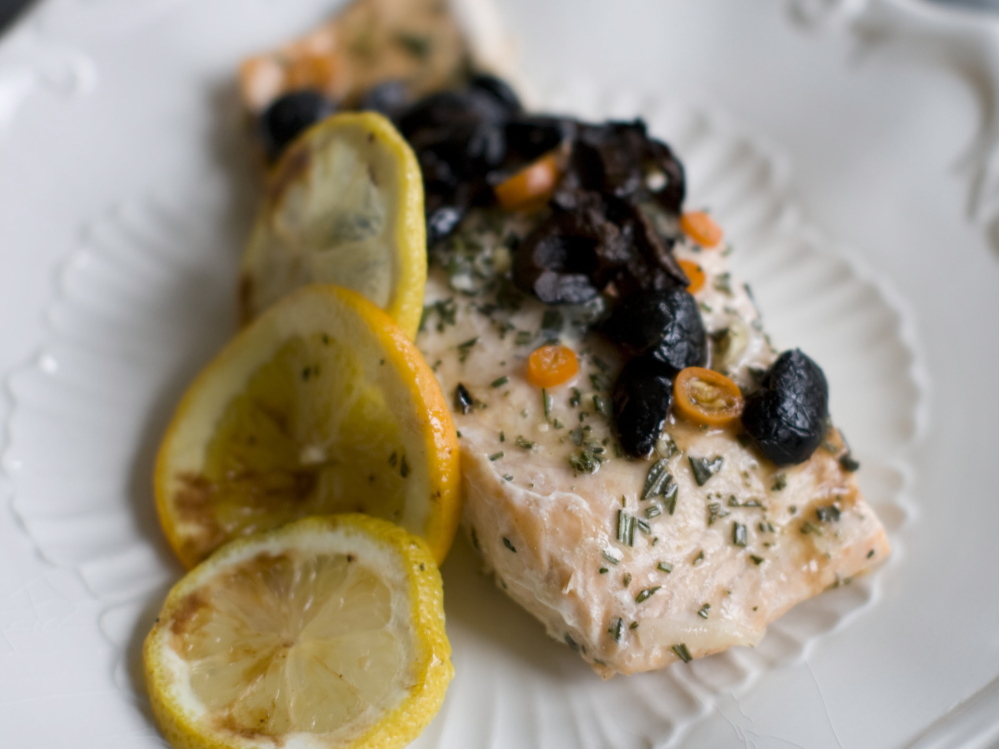 The salmon is served with the olives, chilies and juices spooned on top.