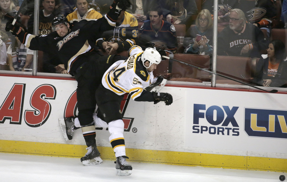 Boston Bruins defenseman Adam McQuaid, right, checks Anaheim Ducks left wing Patrick Maroon during the first period of Tuesday's NHL hockey game.