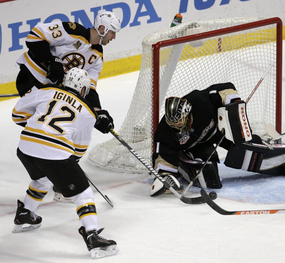 Anaheim Ducks goalie Jonas Hiller, right, blocks a shot by Boston Bruins defenseman Zdeno Chara (33) and right wing Jarome Iginla (12) during the first period.