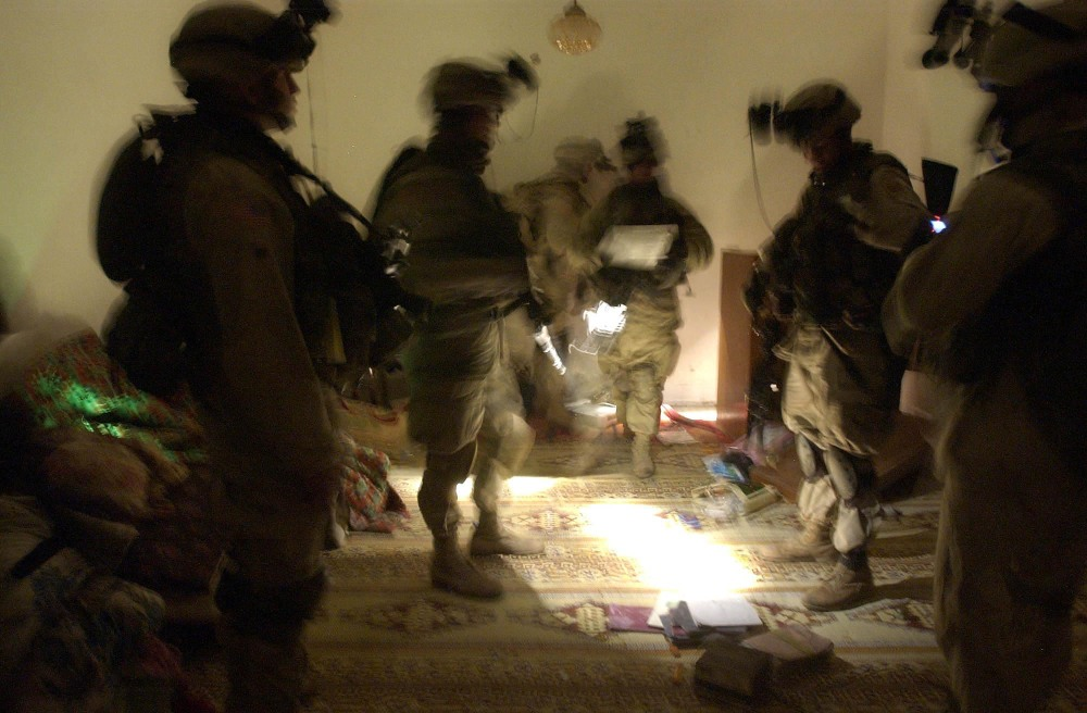 FILE - In this Wednesday, Jan. 14, 2004 file photo, soldiers with the 82nd Airborne Division spread out documents and other objects on the floor while looking for evidence during a raid on an Iraqi house near Fallujah, Iraq. The owner of the house is suspected of being responsible for attacks on coalition forces. In 2014, the city's fall to al-Qaida-linked forces has touched a nerve for the service members who fought and bled there.