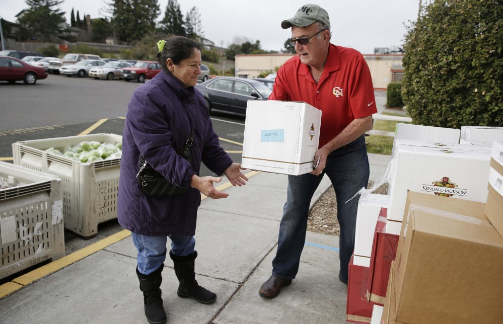 Steve Bosshard hands over a specially prepared box of food to Maria Gonzalez, left, at a food bank distribution in Petaluma, Calif., as part of a research project with Feeding America to try to improve the health of diabetics in food-insecure families.
