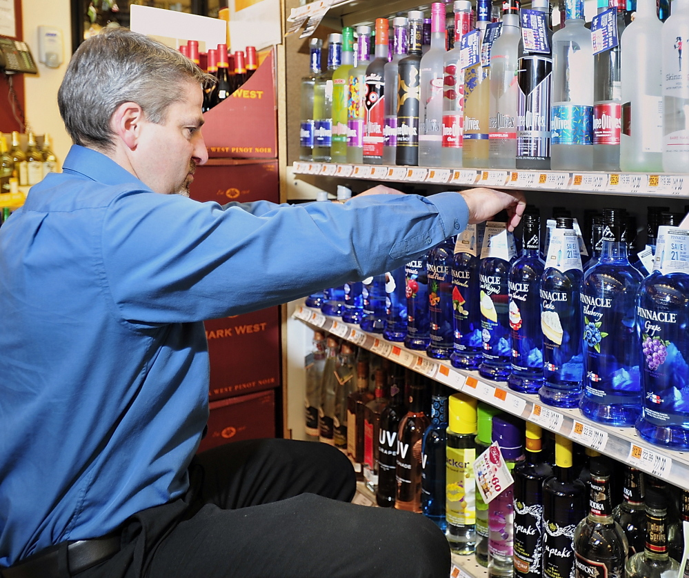 Manager Jim Frey arranges bottles Thursday at Bow Street Market in Freeport. Store owner Adam Nappi said he's glad to continue working with Pine State Trading Co., which was awarded a new state liquor contract.