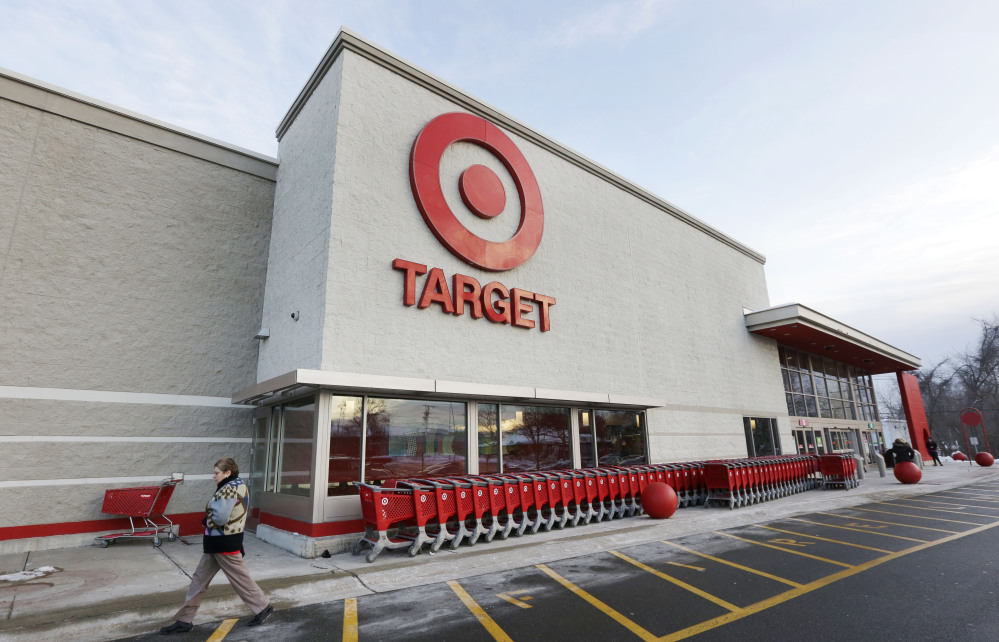 In this Dec. 19, 2013, file photo, a passer-by walks near an entrance to a Target retail store in Watertown, Mass. Target says that personal information ó including phone numbers and email and mailing addresses ó was stolen from as many as 70 million customers in its pre-Christmas data breach.
