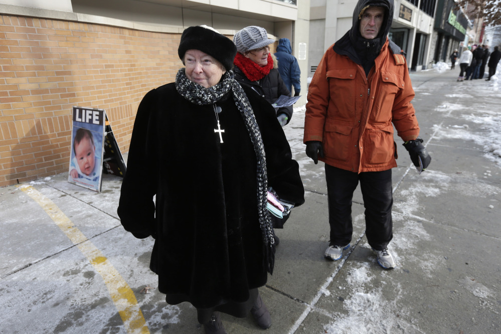 Anti-abortion protester Eleanor McCullen of Boston, left, stands at the painted edge of a buffer zone in December outside a Planned Parenthood clinic in Boston. The buffer, which was the model for a Portland ordinance, is being challenged at the U.S. Supreme Court as an unconstitutional infringement on free speech. Arguments are set for Wednesday.