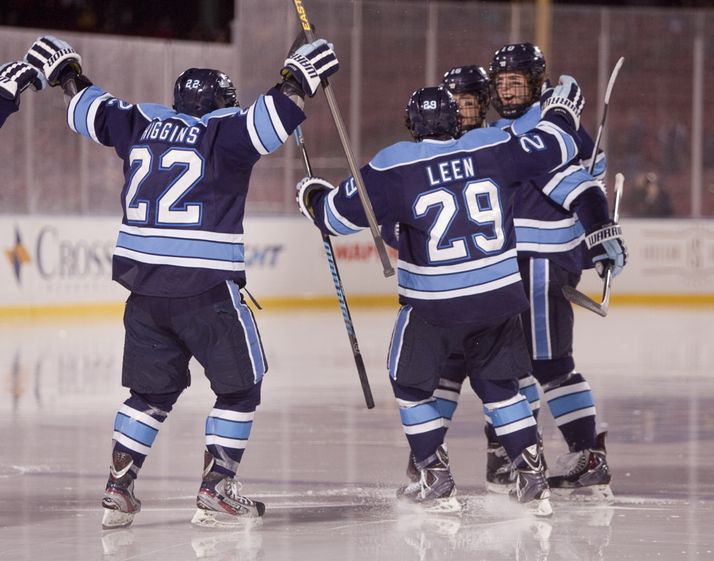 UMaine players celebrate Ben Hutton's first-period goal against Boston University on Saturday.
