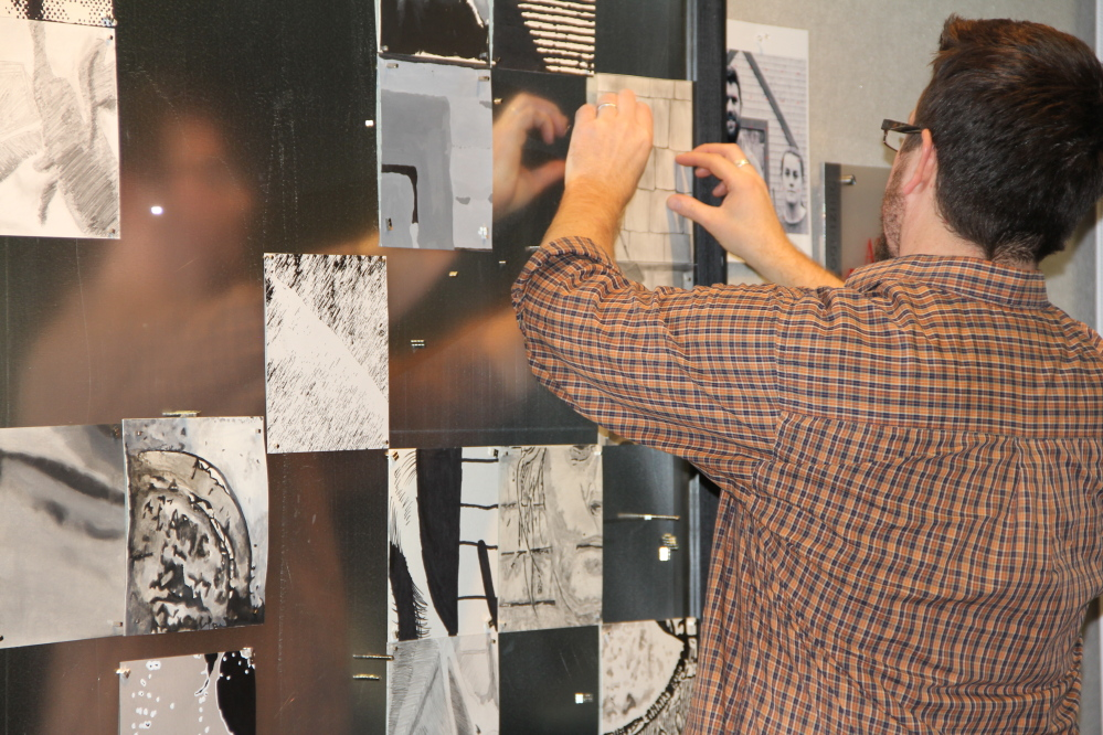"Jason Morgan, an art teacher at Cony High School in Augusta, assembles one of the ""Farmers Edition"" portraits at the Danforth Gallery at the University of Maine at Augusta."
