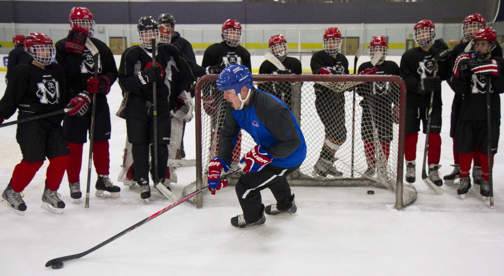 Maine Hockey Academy player development director Adam Nicholas demonstrates a move to members of the Bantam Black team during practice at the University of Maine ice arena in Gorham.