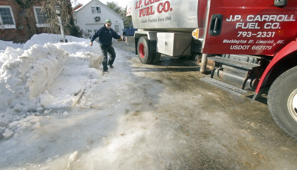 Jim Carroll of J.P. Carroll Fuel Co. slips down an icy driveway while making an oil delivery in Limerick on Tuesday. Carroll is one of four siblings running the company started by their grandfather. In a time of mega-utility mergers, oil delivery remains a family-centered business in Maine.
