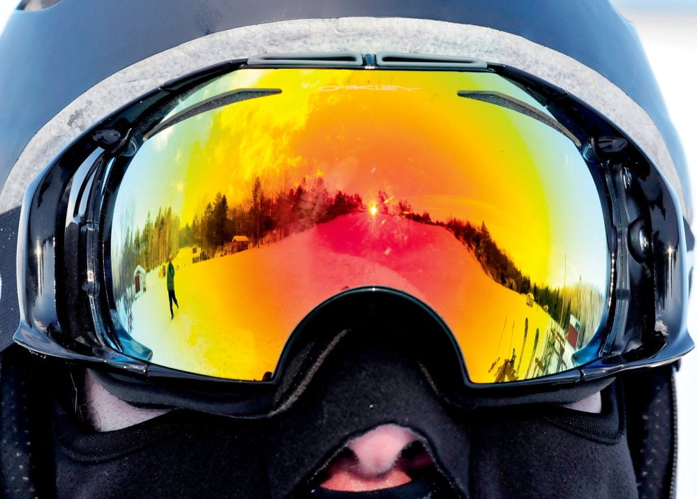 A slope at Titcomb Mountain Ski Area in Farmington is reflected in the goggles of snowboarder Pete Roberts.
