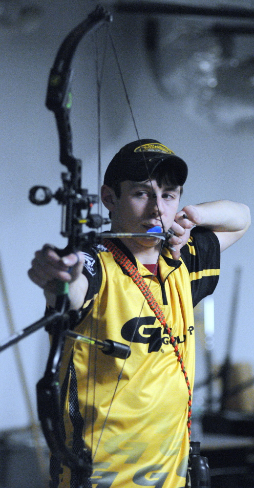 Charlie Weinstein, 17, practices archery on Thursday in a storage room at Maranacook Community Middle School in Readfield.