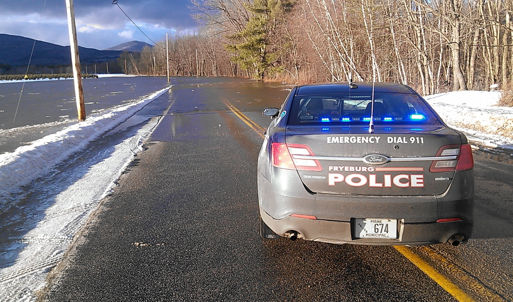 A police car stops on River Street in Fryeburg, just short of a stretch that is flooded by the swollen Saco River on Sunday.