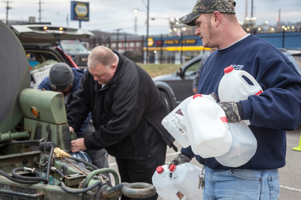 Employees of the South Charleston Public Works Department assist the residents in obtaining cases of water and filling the containers they brought with them on Sunday after a chemical spill Thursday in the Elk River contaminated the public water supply in nine counties.