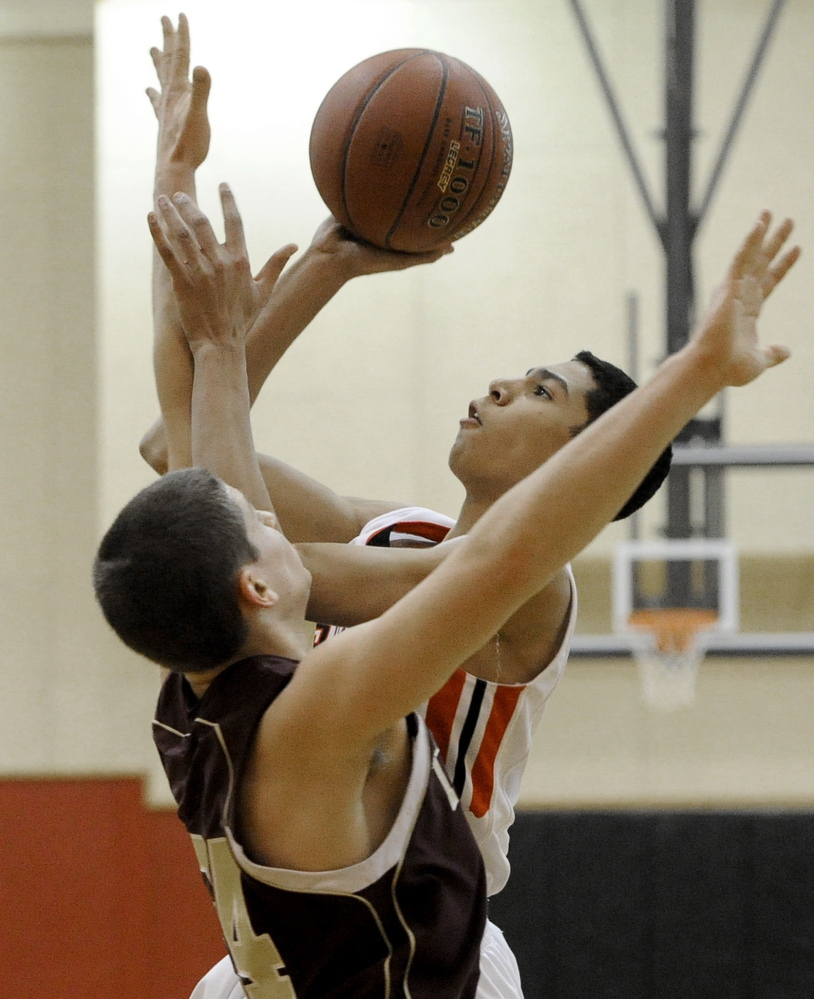 Scarborough's Milani Hicks puts up a shot against Reuben Moses of Thornton Academy during their SMAA basketball game Monday night in Scarborough. The host Red Storm earned a 70-46 victory.