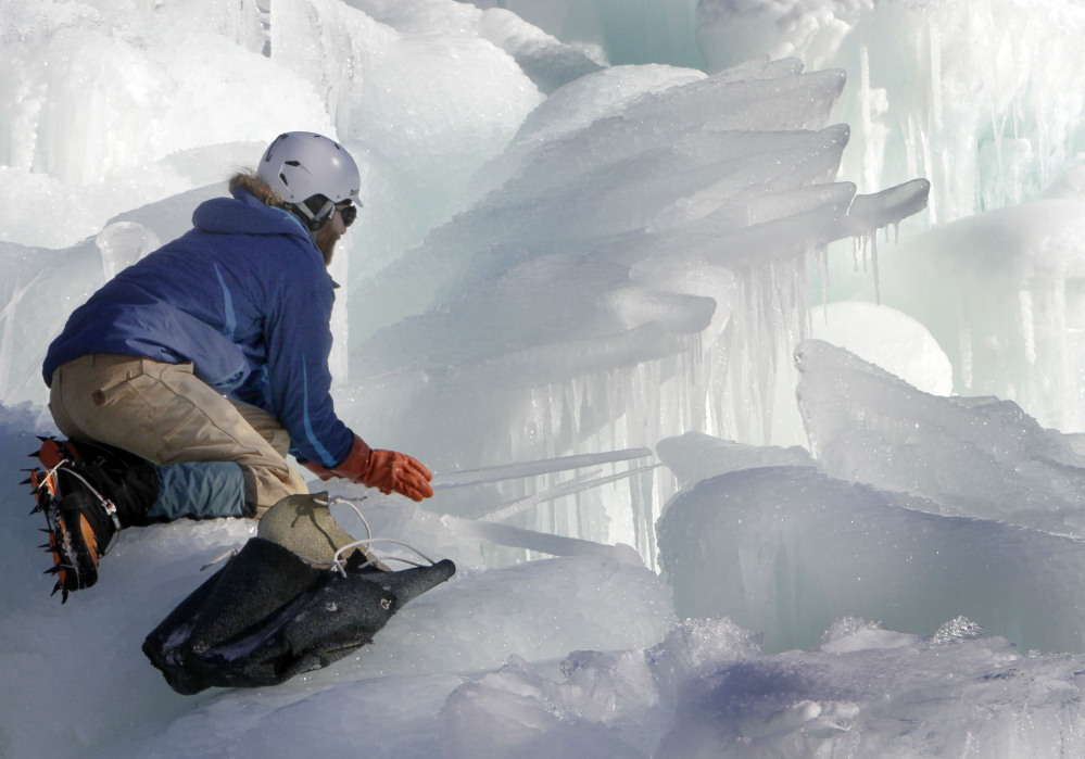 Cory Livingood places icicles on the top of his ice castle at the base of the Loon Mountain ski resort in Lincoln, N.H.