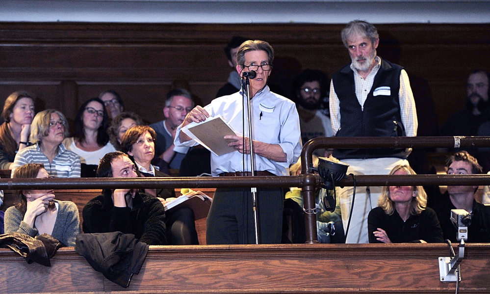 "Surrounded by overflow spectators in the balcony at City Hall, Peter Monro speaks against the ""midtown"" project during the public comments part of the Planning Board meeting Tuesday evening. Standing at right, Dick Stevens awaits his turn to speak."
