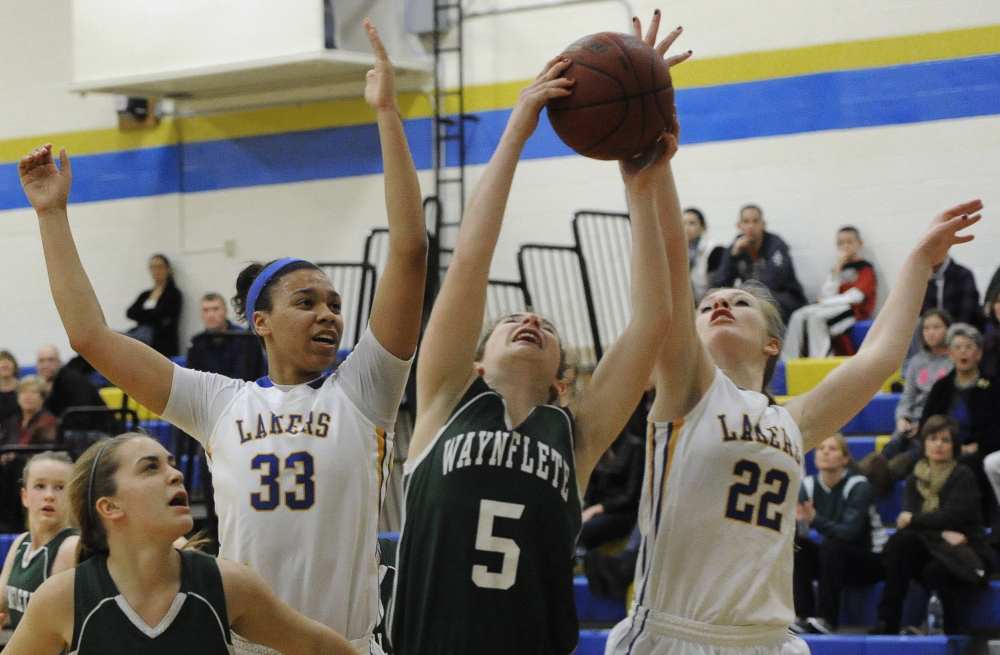 Emily Wasserman of Waynflete pulls down a rebound Tuesday between Tiana-Jo Carter, left, and Miranda Chadbourne of Lake Region during Lake Region's 62-37 victory at Naples.
