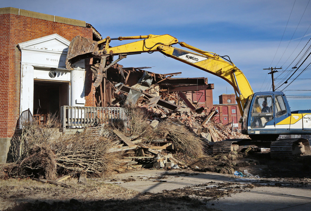 An excavator operator demolishes the entrance to the former headquarters of the Berkshire Hathaway mill, where investor Warren Buffett first made his mark, in New Bedford, Mass.