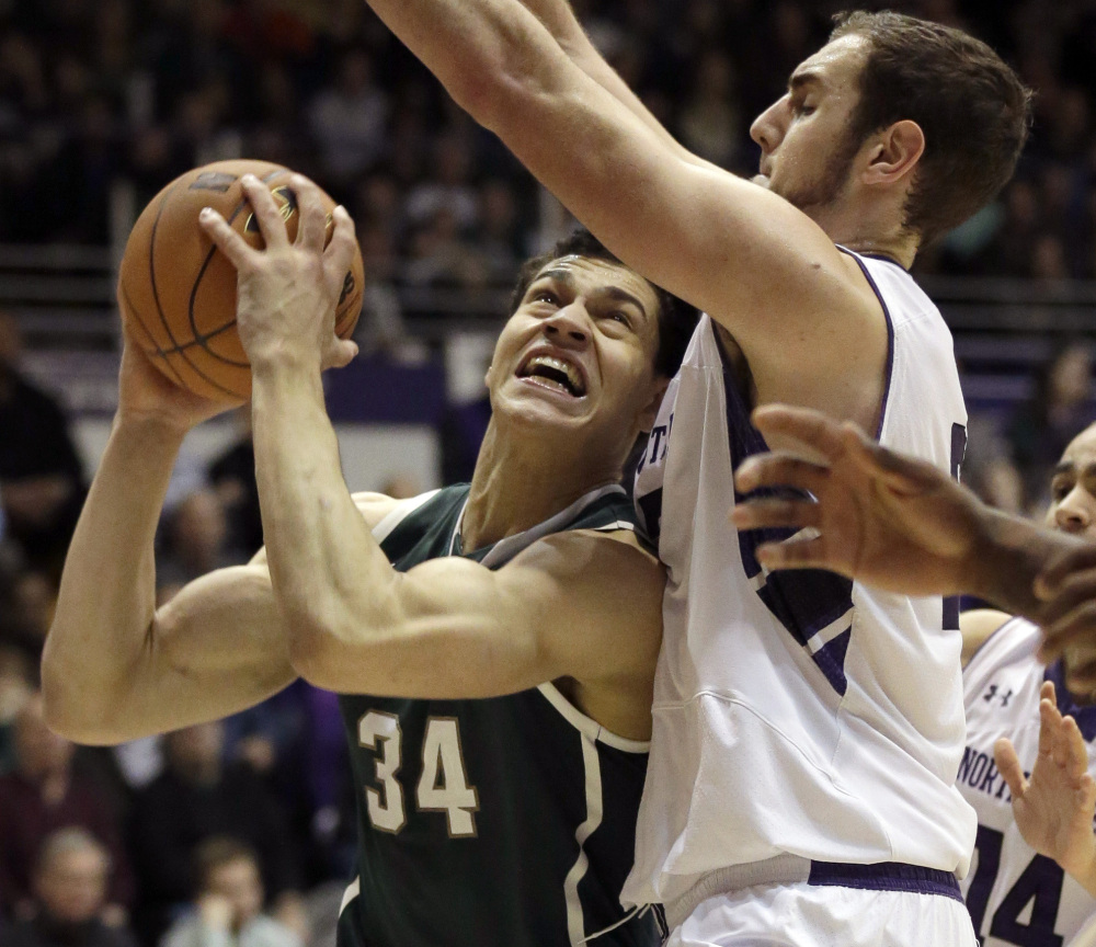 Michigan State forward Gavin Schilling, left, looks to the basket as Northwestern center Alex Olah defends Wednesday night at Evanston, Ill. The Spartans won, 54-40.