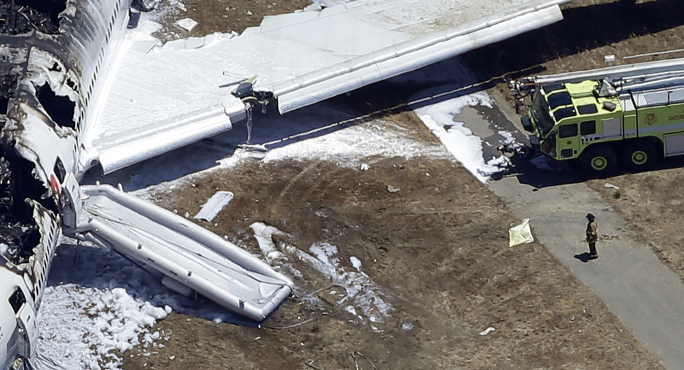 In this July 6, 2013, aerial photo, a firefighter stands by a tarpaulin sheet covering a body near the wreckage of the Asiana Flight 214 jet after it crashed at the San Francisco International Airport in San Francisco