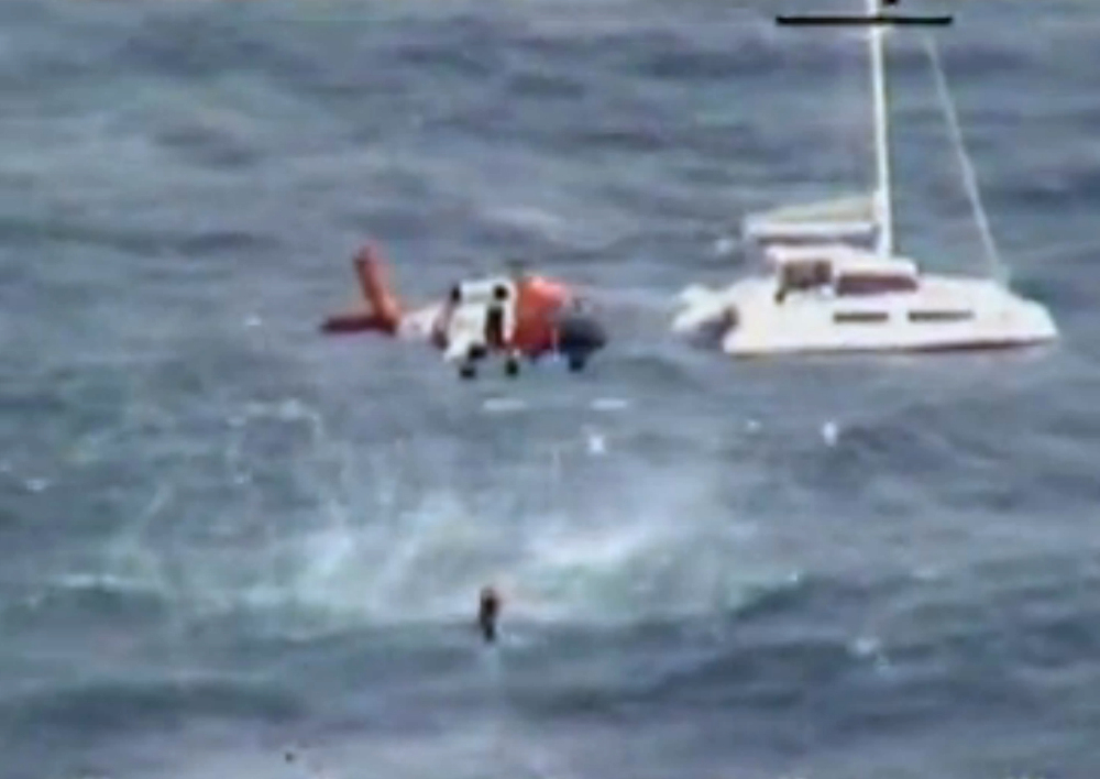In this image from video provided by the U.S. Coast Guard a Coast Guard helicopter crew hoists one of four people from the 42-foot sailboat Be Good Too.