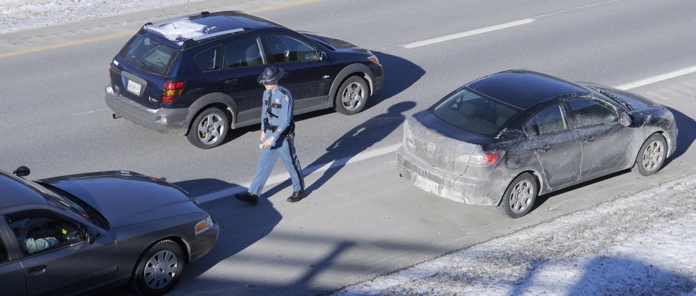 A car drives past Maine State Trooper Chris Rogers during a traffic stop in West Gardiner. Maine law requires a driver to slow down when approaching a parked emergency vehicle and move into an adjacent lane, if it's safe to do so.