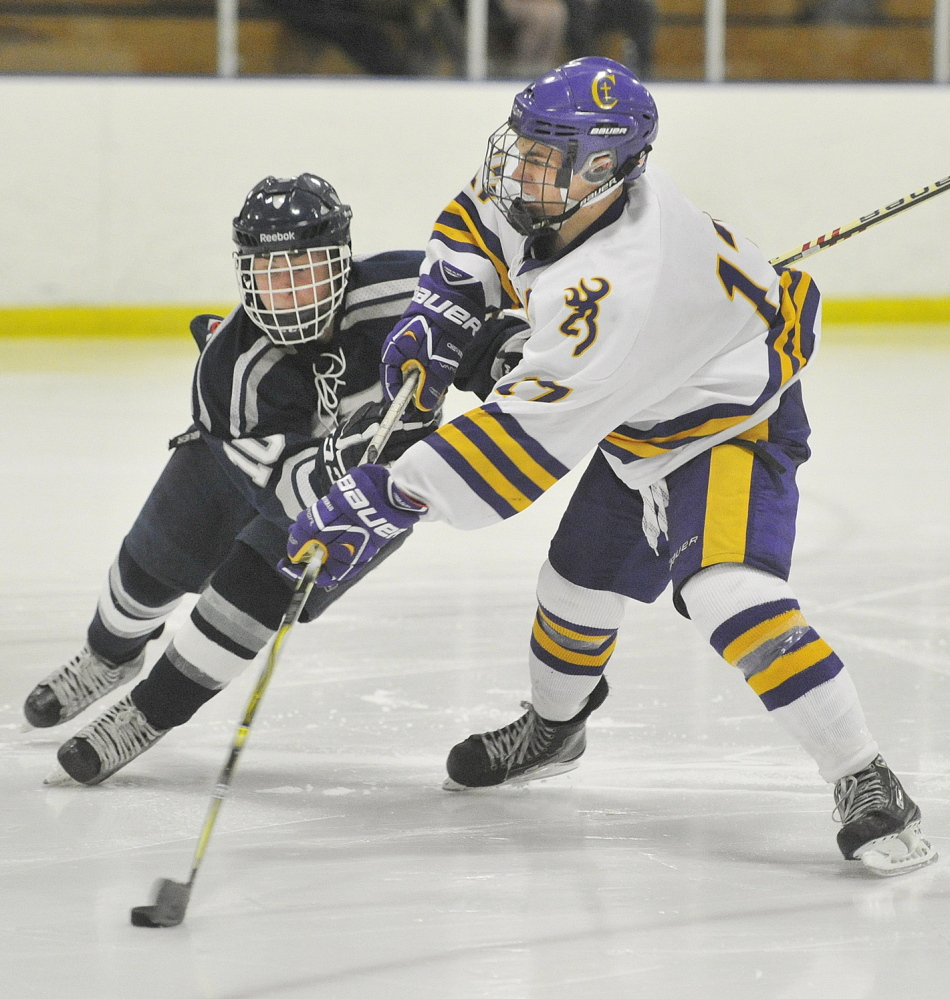 James Hannigan of Cheverus, right, blasts in a slap shot for a short-handed goal Thursday night while defended by Pat Grant of Yarmouth during Cheverus' 7-3 victory at the Portland Ice Arena.