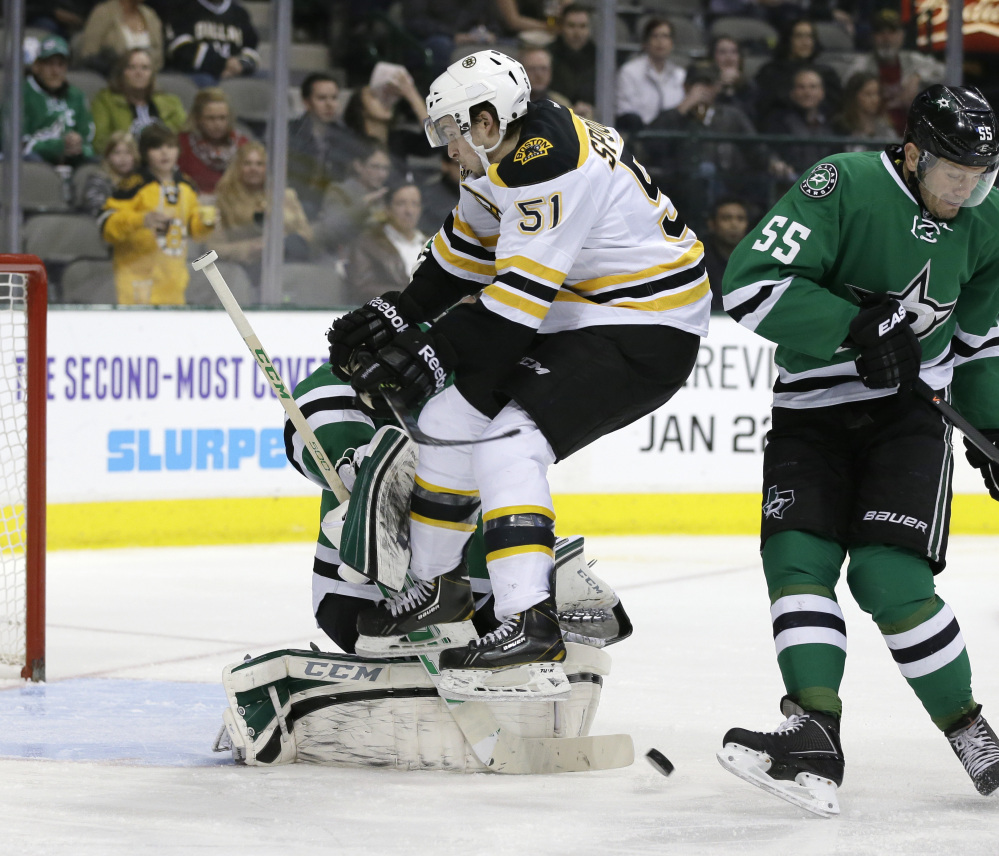 Dallas Stars defenseman Sergei Gonchar, right, helps goalie Kari Lehtonen defend the net as Boston Bruins' Ryan Spooner leaps to clear the way for a shot during the second period of Thursday's game in Dallas, won by the Bruins.