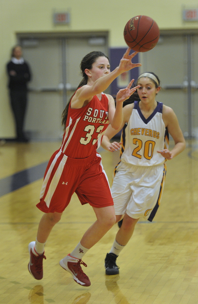 Madeline Hasson of South Portland passes the ball up the court, beating a pressing defense by Cheverus that included Georgia Ford.