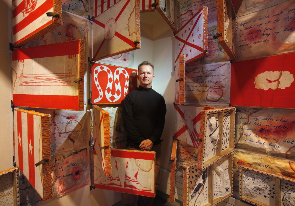 """Artist Kenny Cole with some of his works in the installation """"Parabellum,"""" which is showing in the Zillman Gallery at the University of Maine Museum of Art in Bangor. The show features paintings by Cole and poetry by Chris Crittenden."""