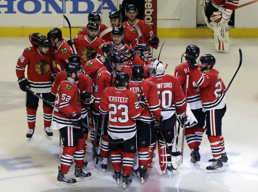 Chicago Blackhawks goalie Corey Crawford (50) celebrates with teammates after the Blackhawks defeated the Boston Bruins 3-2 following their shootout period of an NHL hockey game in Chicago, Sunday, Jan. 19, 2014.