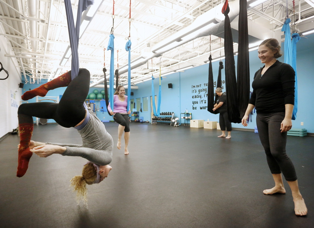 Instructor Kelly Corbin, right, watches as Kathleen Jones of Freeport tries out a pose during an aerial yoga class at Zone 3 Fitness in Scarborough on Sunday.