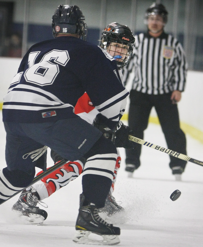 Ricky Ruck of Biddeford sends the puck past Mike Fuller of Portland/Deering. Ruck scored four goals in Biddeford's victory.