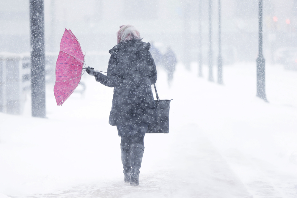 A pedestrian's umbrellas is upset during a winter snowstorm Tuesday, Jan. 21, 2014, in Philadelphia. A storm is sweeping across the Mid-Atlantic and New England. The National Weather Service said the storm could bring 8 to 12 inches of snow to Philadelphia and New York City, and more than a foot in Boston.
