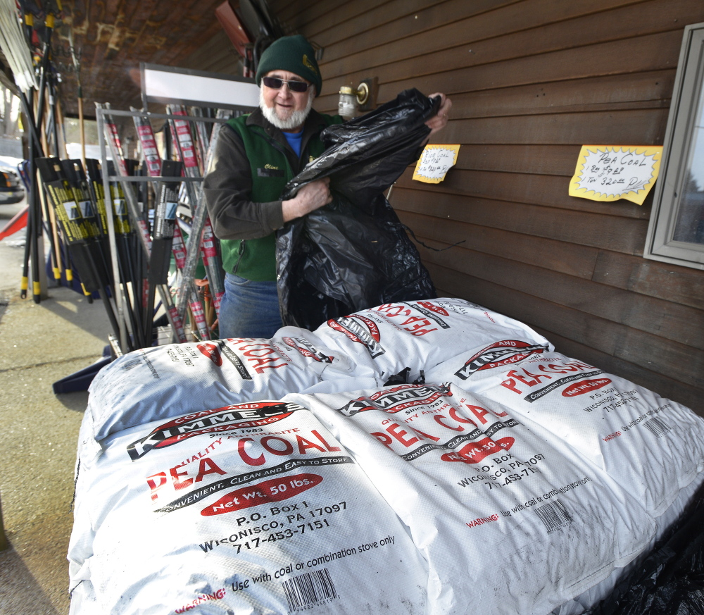 Clint Farnham unwraps a pallet of pea coal Wednesday, Jan. 22, 2014. The Paris Farmers Union in Portland is running out of coal, wood pellets and bio bricks.