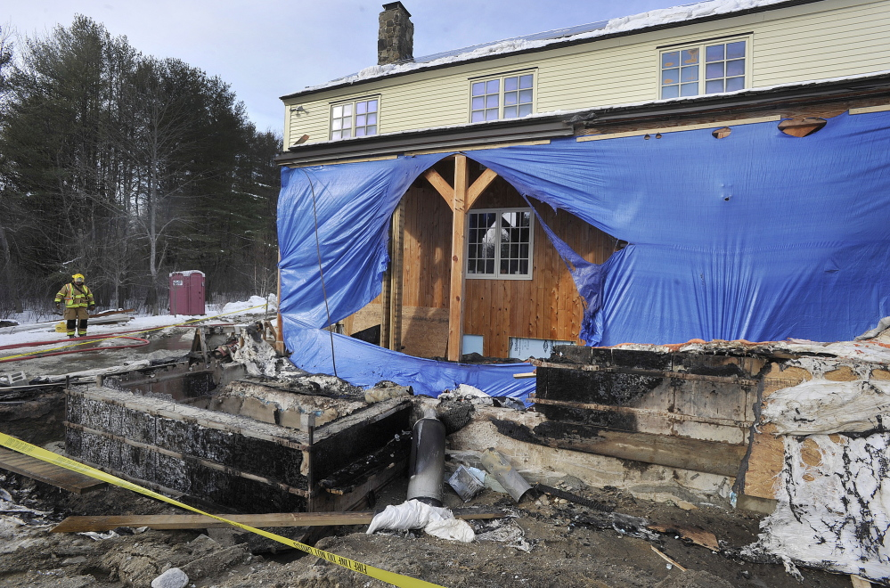 A firefighter monitors the scene after a propane cylinder being used to warm a recently poured concrete foundation malfunctioned Wednesday, spreading fire to some of the addition being built on this house at 527 Ledge Road in Yarmouth.
