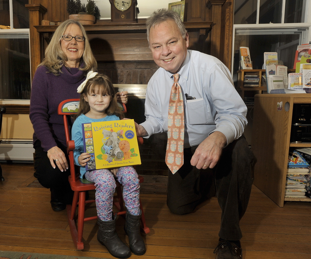 """Giovanna """"Gigi"""" Bella, 5, of York receives Raising Readers' 2 millionth book from Dr. Stephen Brennan and his office manager, Kathy Mackey, at his practice in York on Wednesday. The statewide network has been giving books to children since 2000."""