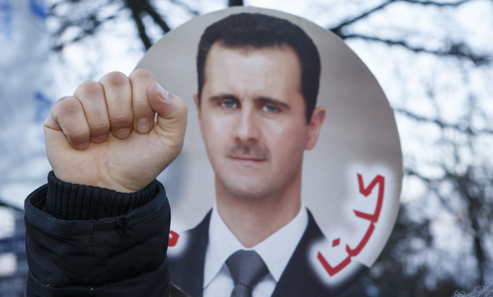 A demonstrator clenches a fist in front of a photo of Syrian President Bashar Assad on Wednesday in Montreux, Switzerland, where the Geneva II peace talks aimed at ending the country's brutal conflict are taking place. When the question of Assad's future as its leader comes up, Syria digs in its heels.