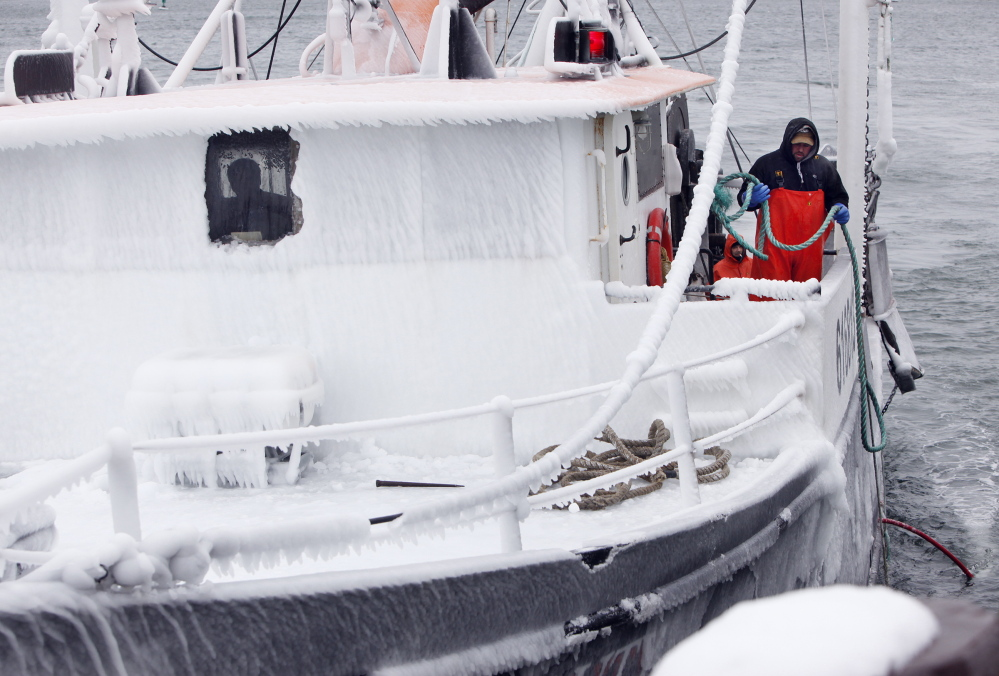 On the side of an iced-over wheelhouse, Larry Rich of Portland prepares to throw a line as the Black Beauty approaches a dock on the Portland waterfront Wednesday morning after returning from an overnight fishing trip.