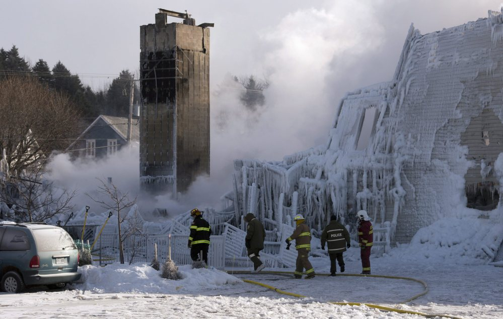 Firefighters work at the scene of a seniors' residence fire on Thursday in L'Isle-Verte, Quebec, Canada. The blaze raged as firefighting equipment froze in -4 Fahrenheit weather.
