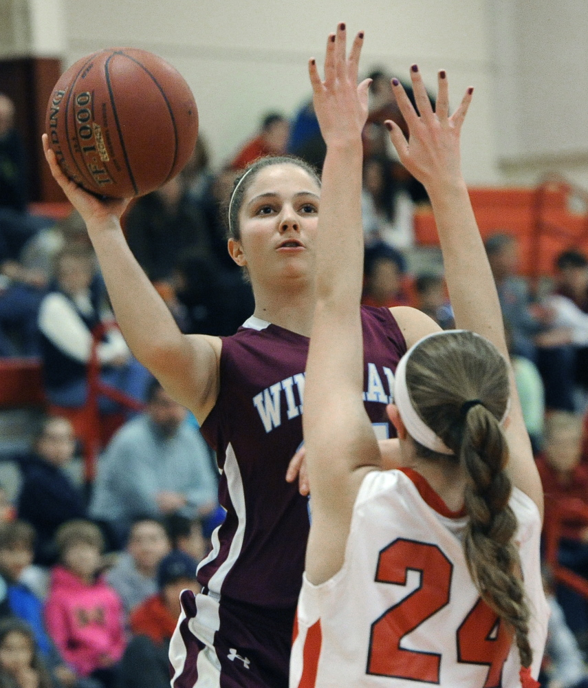 Luisa Sbardella of Windham avoids the charge and takes a shot over Holly Black of South Portland. The Riots used a 31-2 run to put the game away.