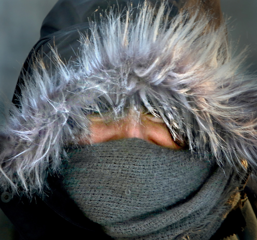 Katie Riley of Portland only has her eyes exposed to the cold as she walks on Congress Street to work Friday morning on January 24, 2014. Riley walks to work everyday except for an occasional ride.