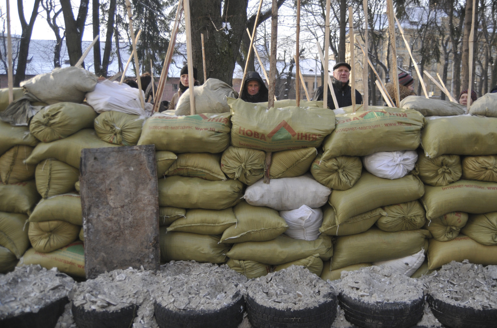 Protesters guard the barricades around seized government headquarters in Lviv, western Ukraine, Friday, in one of several actions that crank up pressure on the government.