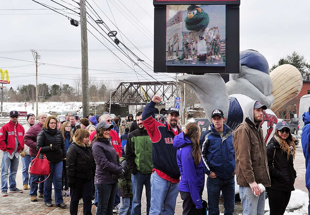 A line of people braved the cold to get their photo taken with three World Series trophies that were won by the Red Sox and displayed Saturday at Hadlock Field following a rally.