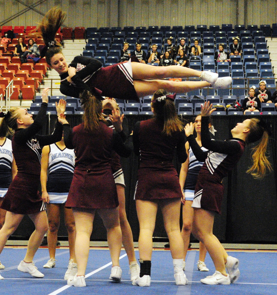Staff photo by Joe Phelan Monmouth Academy cheerleaders spin teammate Emily Lombardo in a barrel roll as the Mustangs compete in the Class C West cheering championship on Saturday January 25, 2014 in the Augusta Civic Center. They finished fifth and qualified for state meet in two weeks in Augusta.