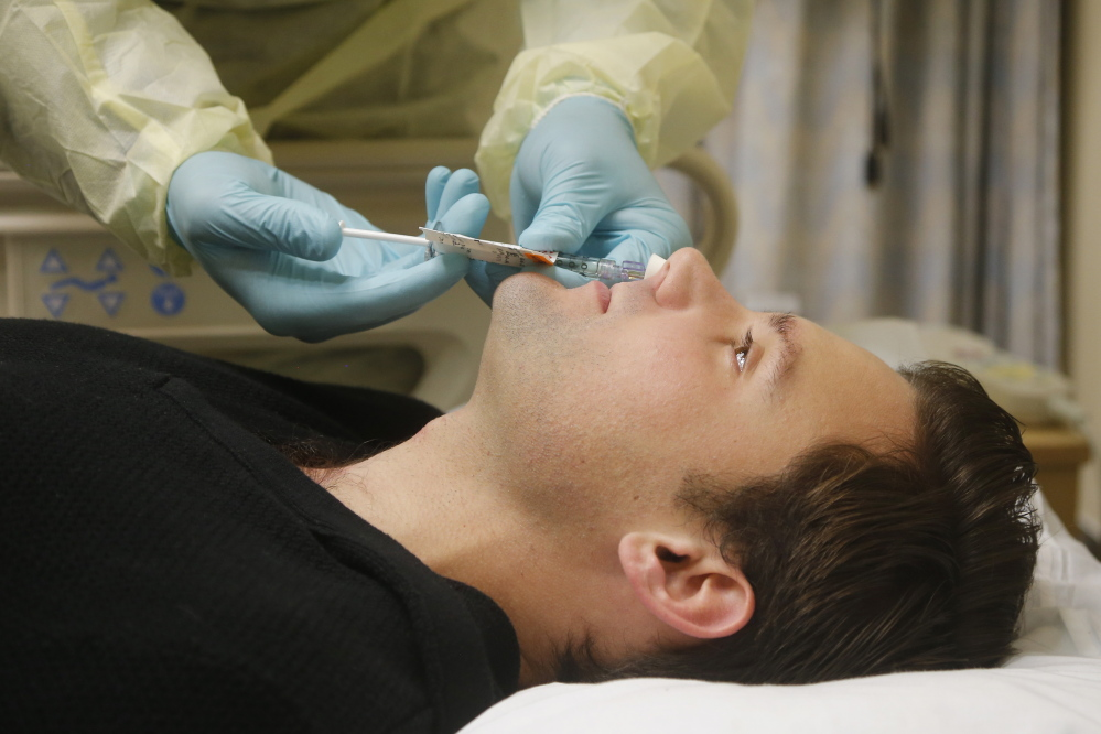 Daniel Bennett, 26, of College Park, Md., has live flu virus sprayed into his nose as part of a study at the National Institutes of Health in Bethesda, Md.