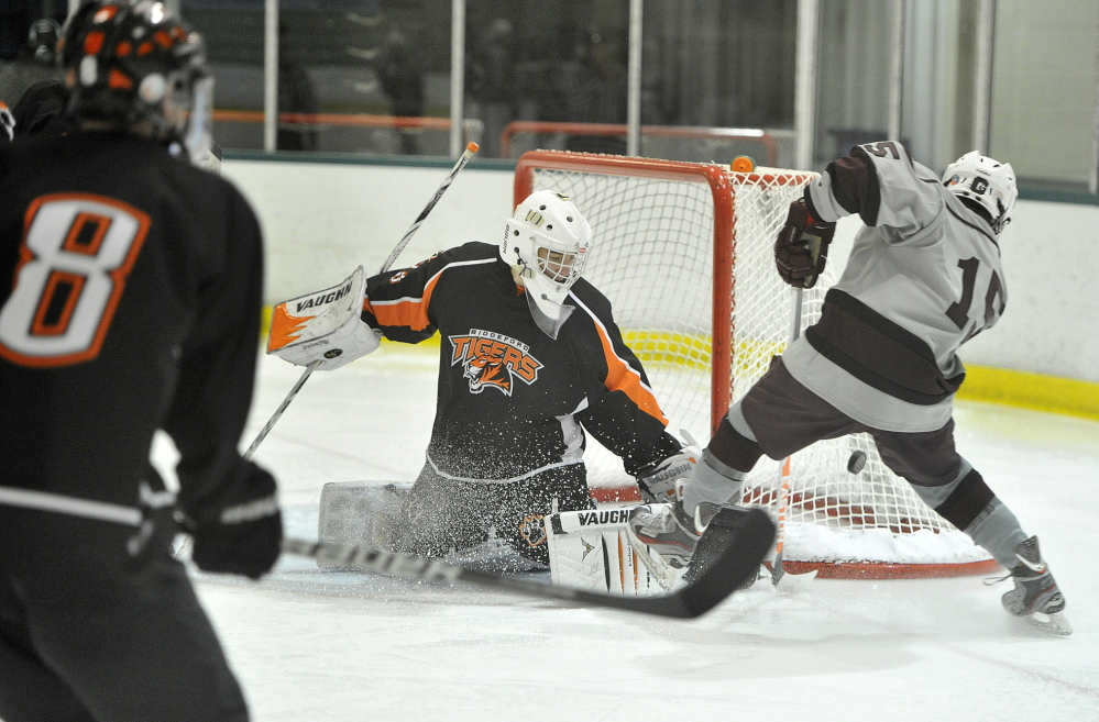 Biddeford goalie Tom Green blocks a point-blank shot by Greely's Nathan Gervais in the second period Monday night at Family Ice Center in Falmouth. Biddeford trailed 4-1 before scoring the final three goals of the game.