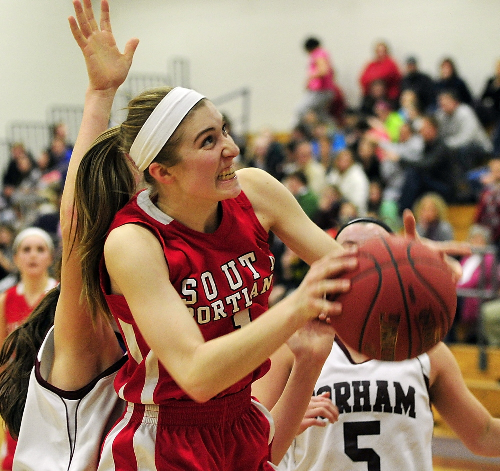 Paige Carter of South Portland puts up a rebound for a basket Tuesday night in a girls' basketball game at Gorham. The Red Riots won in overtime, 64-53.