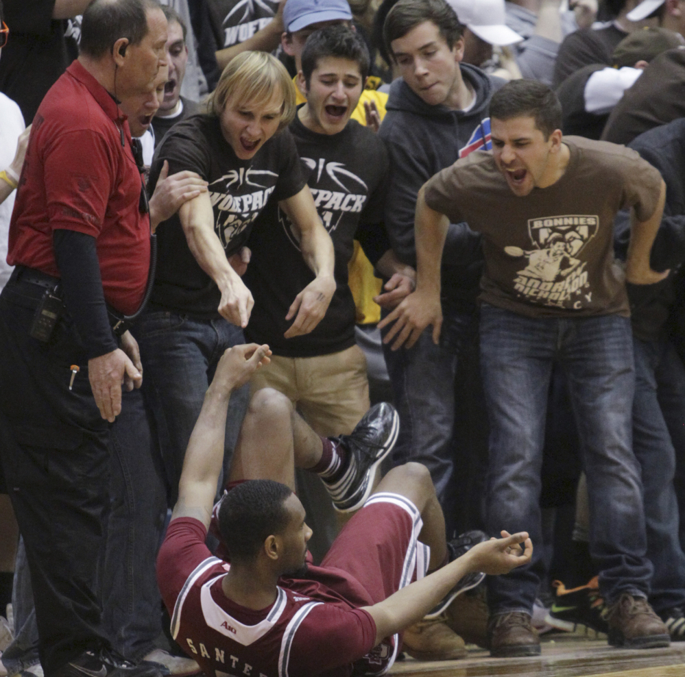 Fans heckle UMass guard Clyde Santee after he tumbled to the court in Wednesday night's game at Olean, N.Y. The 21st-ranked Minutemen were beaten, 78-65.